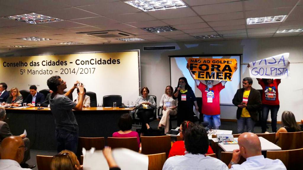 Na primeira reunião do Conselho Nacional das Cidades após o golpe, movimentos de Reforma Urbana fazem ato no Ministério. Sentado à mesa o ministro das cidades do gabinete ilegítimo. Foto: Movimentos de Reforma Urbana.